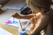 Маленькая девочка живопись акварель на стол — стоковое фото