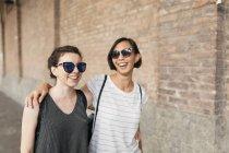 Портрет двух лучших друзей в солнечных очках, идущих перед кирпичным зданием — стоковое фото
