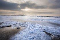 Vue de la plage de sable contre l'eau et des nuages dans le ciel pendant la journée — Photo de stock