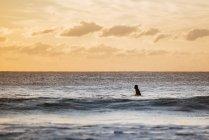 Espagne, Andalousie, Cadix, Conil de la Frontera, Surfeuse surfant au coucher du soleil — Photo de stock