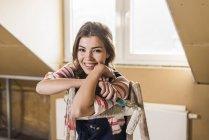 Portrait de jeune femme tenant rouleau de peinture — Photo de stock