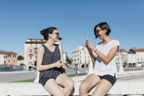 Italy, Padua, young woman taking picture of friend with smartphone — Stock Photo