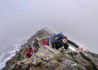 Khumbu de Nepal, Himalaya, región del Everest. Excursionistas escalada en ladera de montaña rocosa - foto de stock