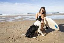 Giovane donna sorridente con tavola da surf e cane sulla spiaggia di sabbia nella giornata di sole — Foto stock