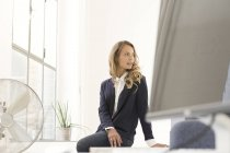 Confident businesswoman sitting on desk in office — Stock Photo
