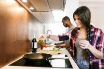 Portrait of young couple cooking at kitchen — Stock Photo
