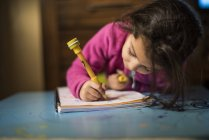 Kleines Mädchen zeichnen und Homerworks zu Hause zu tun — Stockfoto