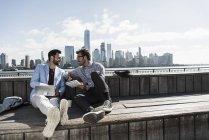 Два підприємців, які працюють в Нью-Джерсі набережній з видом на Манхеттен, США — стокове фото