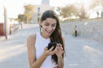 Портрет молодой улыбающейся женщины с помощью смартфона — стоковое фото