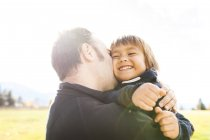 Portrait of man embracing smiling boy outdoors — Stock Photo