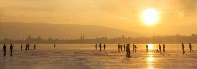 Deutschland, Bodensee-Hege, Silhouetten von Schlittschuhläufern und Spaziergängern vor Reichenau bei Sonnenuntergang — Stockfoto