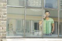 Joven profesional de hablar por teléfono en la ventana en oficina - foto de stock
