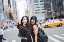 Портрет двух молодых, улыбаясь женщины, стоя на улице — стоковое фото