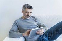 Retrato del hombre maduro usando la tableta en el sofá - foto de stock