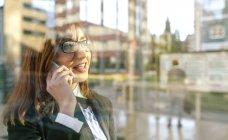 Femme d'affaires, parler au téléphone en face de la vitre — Photo de stock