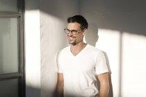 Портрет молодого человека в очках, прислонившегося к стене в офисе — стоковое фото