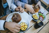 Cropped view of female hands with hamburgers and french fries — Stock Photo