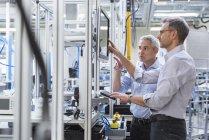 Businessmen talking at computer monitor — Stock Photo