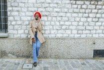 Donna che parla al telefono davanti al muro di mattoni — Foto stock