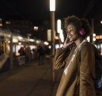 Giovane donna sorridente che ascolta musica con le cuffie mentre aspetta alla fermata del tram — Foto stock