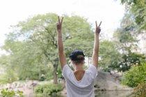 Молода жінка щаслива, робити знак перемоги в центральному парку Манхеттен Нью-Йорк, США — стокове фото