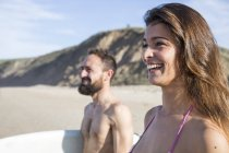 Young couple with surfboard at the beach, looking aside — Stock Photo