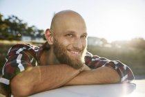 Portrait of bald young man with beard leaning on car roof — Stock Photo