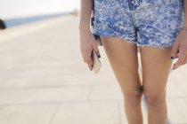Обрізаний портрет молодої жінки, що тримає смартфон — стокове фото