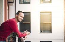 Porträt von lächelnden Mann auf Balkon mit Kaffeetasse — Stockfoto