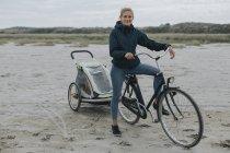 Нідерланди, Schiermonnikoog, жінка з велосипеда і причепа на пляжі — стокове фото