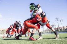 Американского футболиста атакует оппонент во время матча — стоковое фото