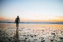 Spagna, Andalusia, Cadice, Conil de la Frontera, Surfista con tavola da surf al tramonto . — Foto stock