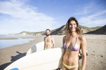 Couple of surfers with surfboards at sandy beach smiling at camera — Stock Photo