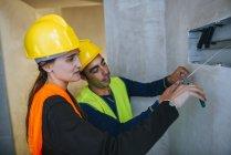 Eletricista de casal trabalhando com cabos eléctricos do trabalho — Fotografia de Stock
