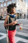 Portrait de jeune femme marchant avec smartphone et boisson — Photo de stock