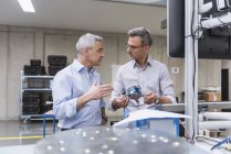 Hommes d'affaires examinant le produit — Photo de stock