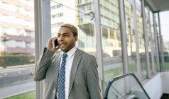 Uomo d'affari in piedi sulla scala mobile e parlare su smartphone — Foto stock