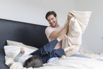 Happy father and son playing in bed — Stock Photo