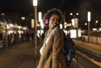 Smiling young woman with headphones and backpack waiting at tram stop — Stock Photo