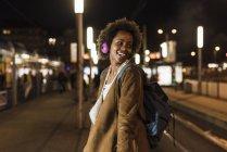 Усміхаючись молода жінка з навушниками і рюкзак очікування на трамвайній зупинці — стокове фото