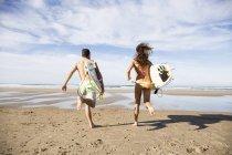 Пара серферів з дошки для серфінгу, працює в океан біля піщаного пляжу — стокове фото
