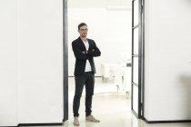 Jeune homme d'affaires permanent au bureau avec les bras croisés — Photo de stock