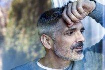 Обрізаний портрет зрілою людиною, стоячи біля області вікна — стокове фото