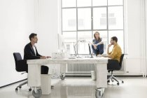 Young colleagues sitting together in modern office — Stock Photo