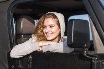 Retrato de uma jovem feliz inclinada para fora da janela do carro — Fotografia de Stock