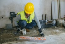 Workers placing flooring with a mallet. — Stock Photo