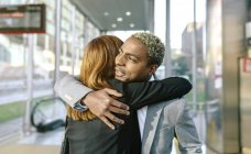 Young businessman and businesswoman embracing at metro station — Stock Photo