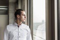Портрет молодого бизнесмена, смотрящего в окно — стоковое фото
