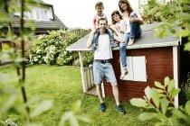 Familia feliz sentado en el tejado de su caseta de jardín - foto de stock