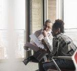 Старший менеджер обсуждает документы с молодым коллегой — стоковое фото